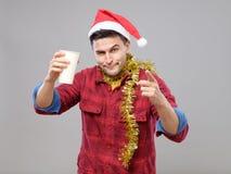 Grappige jonge gedronken mens die Kerstmanhoed dragen die een document kop houden stock afbeelding
