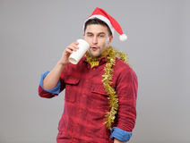 Grappige jonge gedronken mens die Kerstmanhoed dragen die een document kop houden stock afbeeldingen