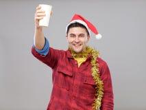 Grappige jonge gedronken mens die Kerstmanhoed dragen die een document kop houden stock fotografie