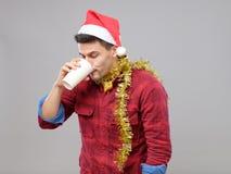 Grappige jonge gedronken mens die Kerstmanhoed dragen die een document kop houden royalty-vrije stock afbeeldingen