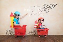 Grappige jonge geitjes die stuk speelgoed auto drijven binnen royalty-vrije stock afbeeldingen