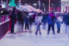 Grappige jonge geitjes, families samen in avondtijd in openlucht in het park op de winter het schaatsen piste Vage foto stock afbeelding