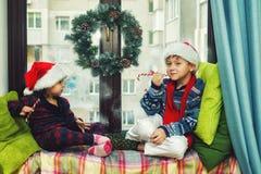Grappige jonge geitjes in het huis die op Kerstmis wachten stock fotografie
