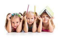 Grappige jonge geitjes met boek, potloden en verven royalty-vrije stock afbeeldingen