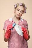 Grappige jonge huisvrouw die met handschoenen scrubberr houden Royalty-vrije Stock Foto