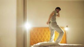 Grappige jonge mens die op bed in de avond vóór slaap dansen stock footage