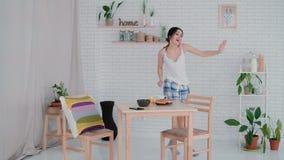 Grappige jonge vrouw die in keuken dansen die pyjama's in de ochtend dragen Het donkerbruine meisje in vrolijke stemming luistert royalty-vrije stock foto's
