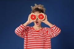 Grappige jonge vrouw met de helften van grapefruit op kleurenachtergrond stock foto's
