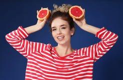 Grappige jonge vrouw met de helften van grapefruit op kleurenachtergrond stock afbeeldingen