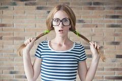 Grappige jonge vrouw met steunen op zijn tanden op bakstenen muurbac Royalty-vrije Stock Afbeelding