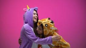 Grappige jonge vrouwen die eenhoorn en girafpyjama's, het lachen, vermaak dragen stock videobeelden
