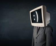 Grappige jonge zakenman met een monitor op zijn hoofd en smiley Stock Afbeeldingen