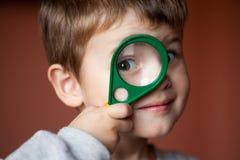Grappige jongen die door vergrootglas met verrassing kijken stock afbeeldingen