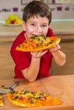 Grappige jongen die het grote stuk van pizza eten royalty-vrije stock afbeelding