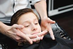 Grappige jongen in een zwarte salonkaap in de herenkapper De kapper past het scheren schuim met behulp van de het scheren borstel royalty-vrije stock fotografie