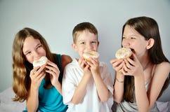 Grappige jongen en twee tienermeisjes die donuts eten Close-up Royalty-vrije Stock Foto