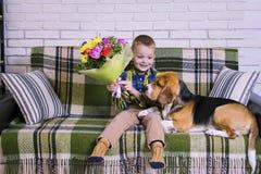 Grappige jongen met een boeket van bloemen en een hondbrak Stock Afbeeldingen