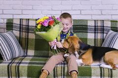 Grappige jongen met een boeket van bloemen en een hondbrak Royalty-vrije Stock Fotografie