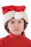 Grappige jongen met rode hoed die van Kerstmis een gezicht trekt Stock Afbeelding