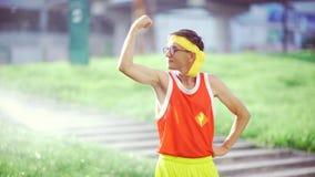 Grappige kerel buitenissige het glimlachen tonende spieren in handen na training i stock videobeelden