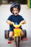 Grappige kind berijdende driewieler Stock Foto's