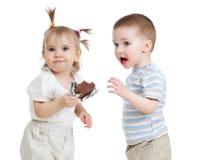 Grappige kinderen die chocolade eten die op wit wordt geïsoleerdn Stock Foto's