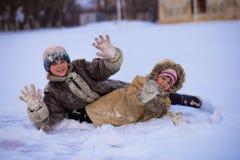Grappige kinderen die en op de sneeuwwinter spelen lachen stock afbeeldingen