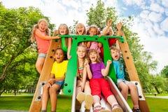 Grappige kinderen op speelplaatshelling met omhoog wapens Stock Foto