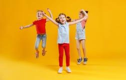 Grappige kinderenmeisjes die op gekleurde gele achtergrond springen Stock Afbeeldingen