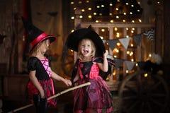 Grappige kinderenmeisjes in heksenkostuum voor donkere backg van Halloween royalty-vrije stock afbeelding