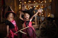 Grappige kinderenmeisjes in heksenkostuum voor donkere backg van Halloween stock foto's