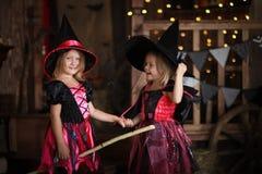 Grappige kinderenmeisjes in heksenkostuum voor donkere backg van Halloween stock fotografie
