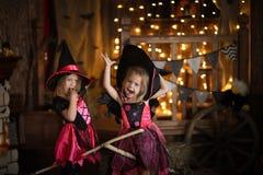Grappige kinderenmeisjes in heksenkostuum voor donkere backg van Halloween royalty-vrije stock afbeeldingen