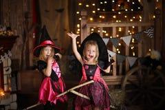 Grappige kinderenmeisjes in heksenkostuum voor donkere backg van Halloween royalty-vrije stock fotografie