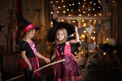 Grappige kinderenmeisjes in het spel van het heksenkostuum voor Halloween-dark royalty-vrije stock foto
