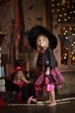 Grappige kinderenmeisjes in het spel van het heksenkostuum voor Halloween-dark Royalty-vrije Stock Afbeeldingen