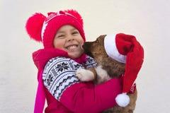 Grappige kleine baby in de tekkel van Santa Claus en van de hond stock foto
