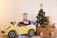 Grappige kleine het glimlachen jonge geitjes die stuk speelgoed auto met Kerstboom drijven Het gelukkige kind op kleurenmanier kl Royalty-vrije Stock Fotografie
