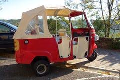 Grappige kleine retro heldere rode three-wheeled convertibele microcar royalty-vrije stock fotografie