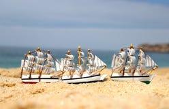 Grappige kleine stuk speelgoed varende schepen op het strand Stock Afbeeldingen