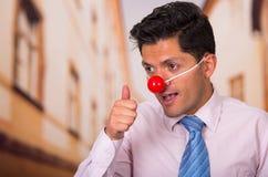 Grappige knappe zakenman met rode plastic neus met zijn duim die omhoog iets goedkeuren Royalty-vrije Stock Afbeelding