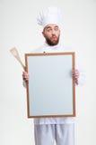 Grappige mannelijke chef-kokkok die lege raad houden Stock Foto's