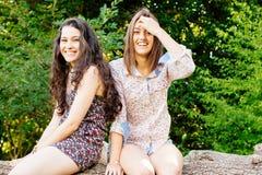 Grappige meisjes die op een boomstam zitten Stock Foto's