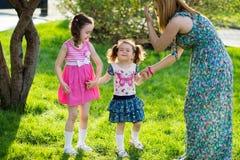 Grappige meisjes die op het gazon met haar moeder lopen De zusters spelen samen met mamma Moeder Zorg Gelukkige Familie stock foto