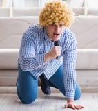Grappige mens het zingen liederen in karaoke thuis royalty-vrije stock afbeelding