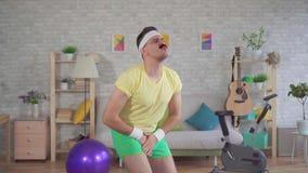 Grappige mensenverliezer die thuis geschiktheid met behulp van elastiekjes doet stock videobeelden