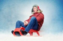 Grappige mensenvlieg op een slee in de sneeuw, de pret van de conceptenwinter Royalty-vrije Stock Fotografie