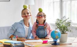 Grappige moeder en kinddochter die thuiswerk het schrijven en readi doen royalty-vrije stock afbeeldingen