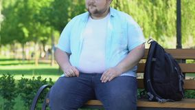 Grappige mollige mannelijke zitting op bank in park en merkwaardig het bekijken voorbijgangers stock footage