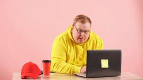 Grappige mollige mens in geel sweatshirt die laptop met grappig buitenissig grimas met behulp van stock videobeelden